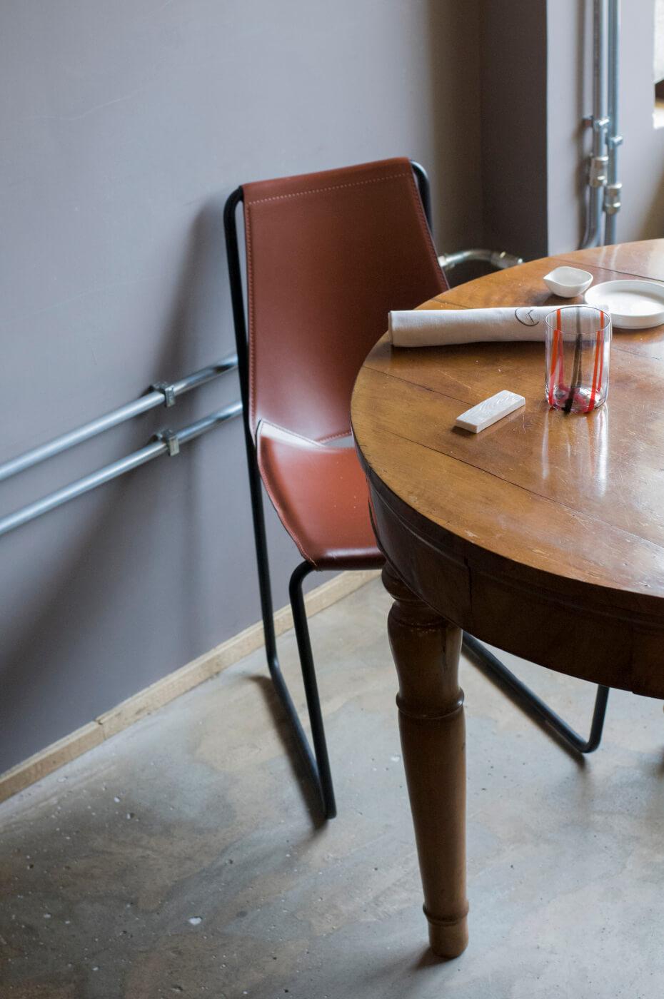 Particolare sedia Apelle con gambe in metallo nero e seduta in cuoio marrone