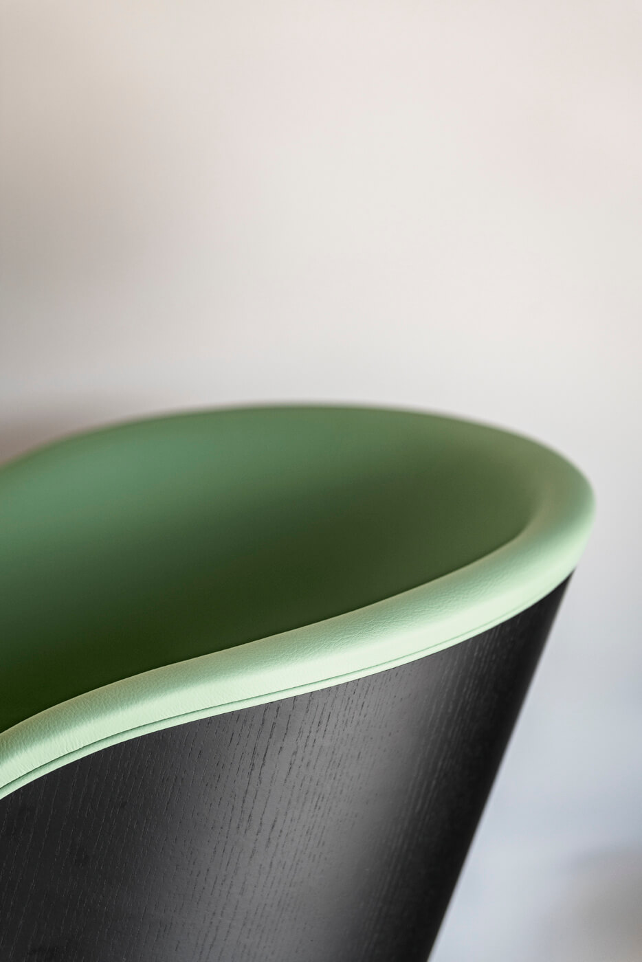 Danny armchair detail with black wood shell back and green leather seat
