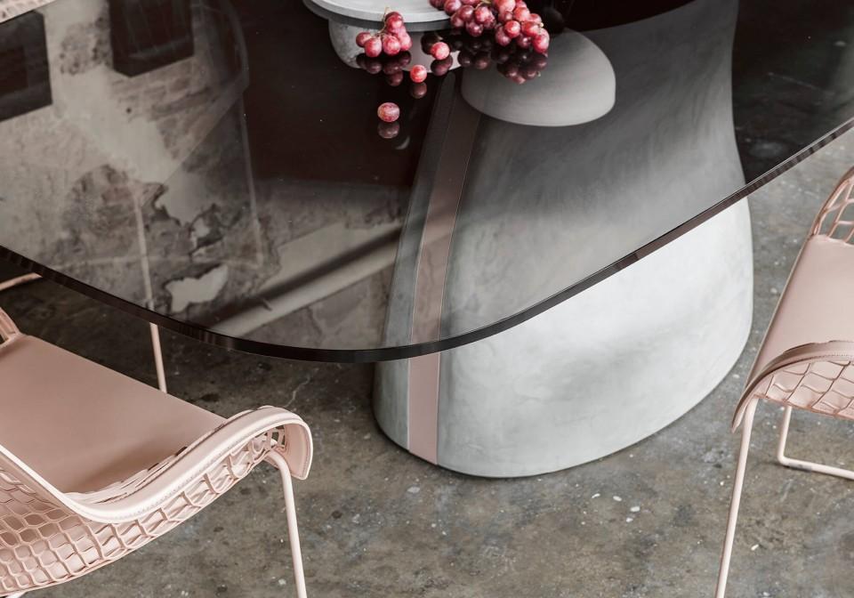 Dettaglio del tavolo Gran Sasso con base in baydur effetto cemento spatolato e inserto metallico rosa cipria