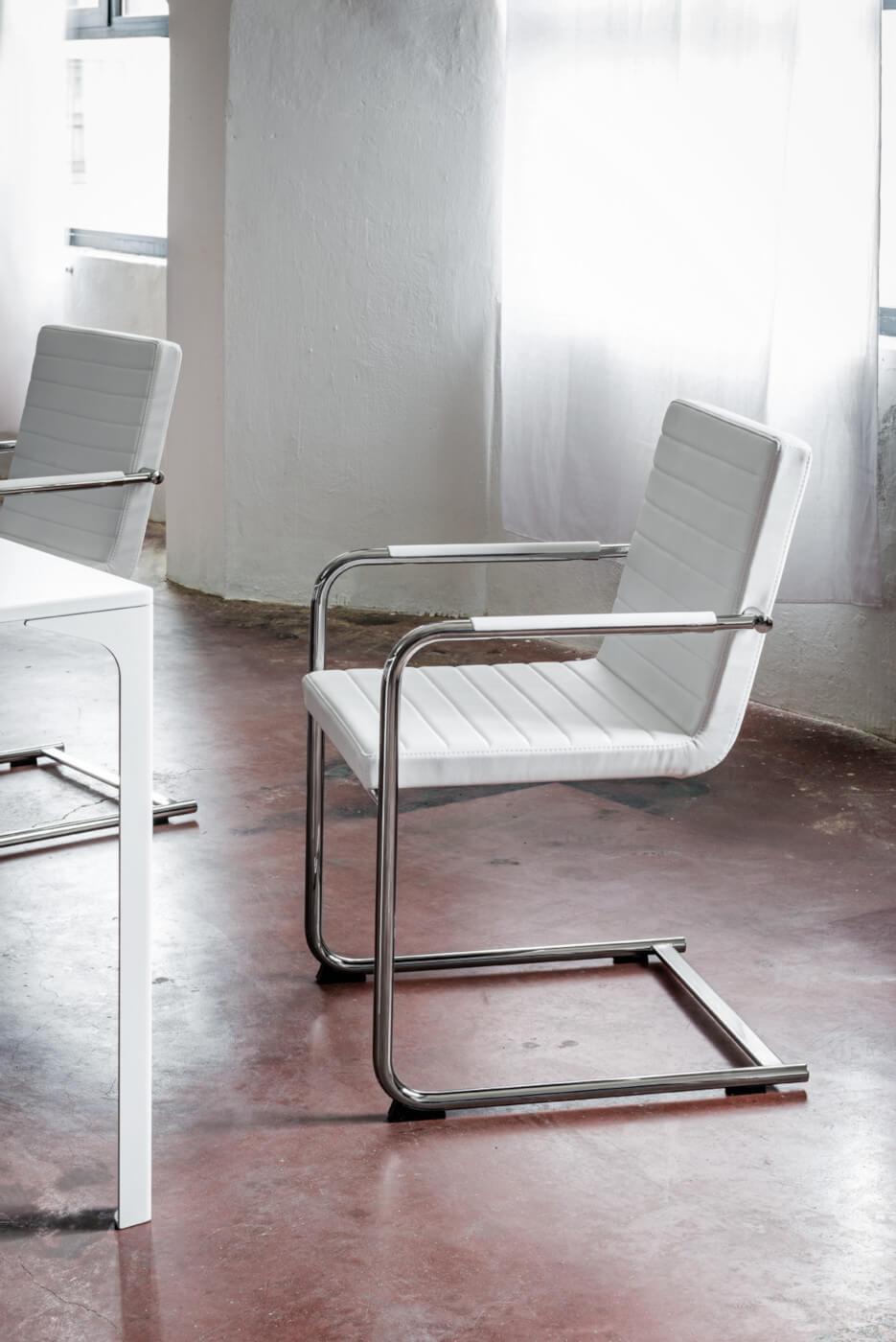 Chaise design H5 avec assise rembourrée revêtue en tissu blanc, la structure est en métal.