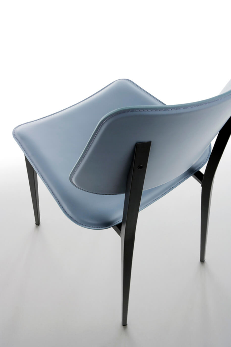 Detail of the Joe back chair in light blue hide and metal base