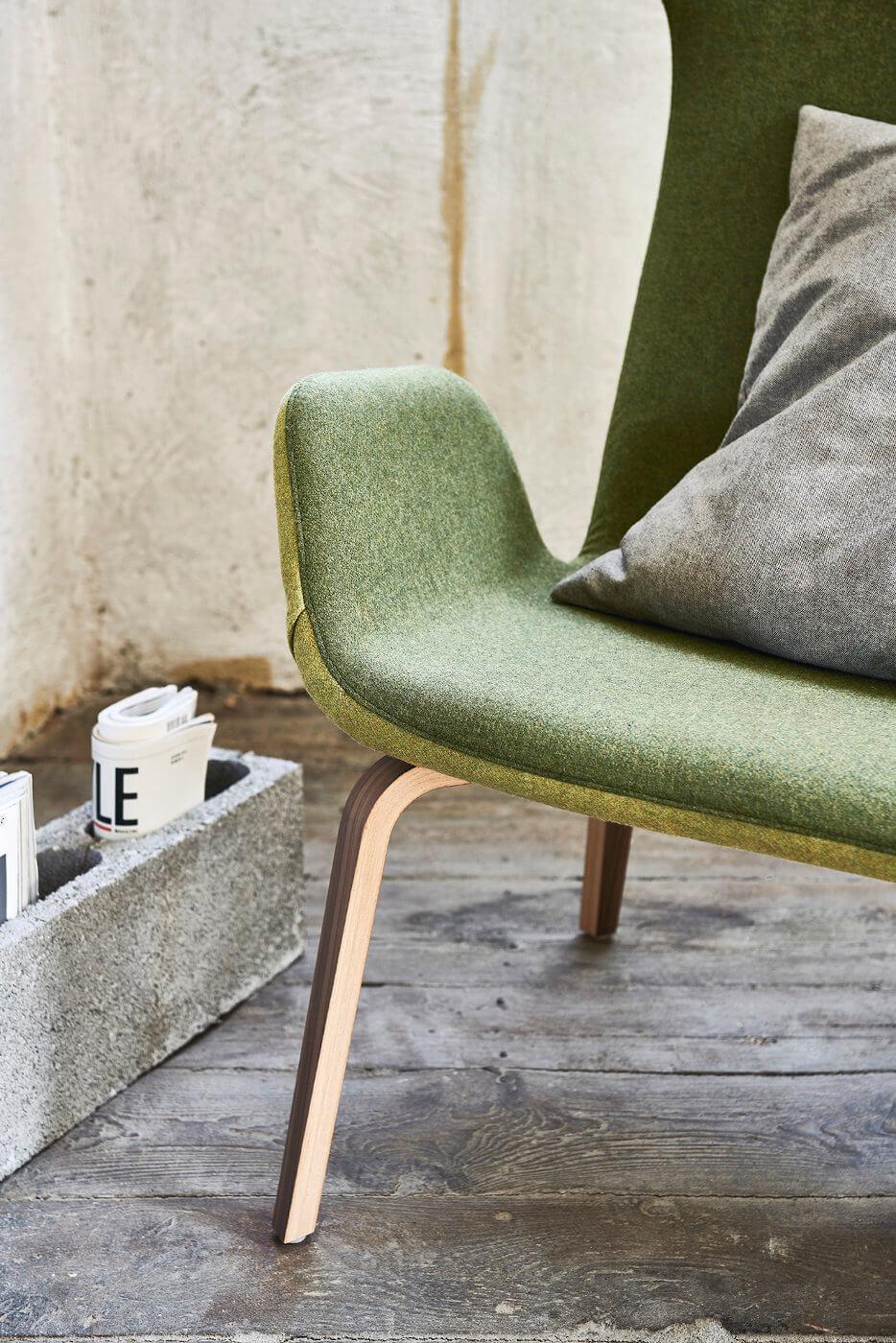 Particolare poltrona Light con seduta in tessuto verde e base in legno. Il modello presenta il retro in tessuto verde chiaro