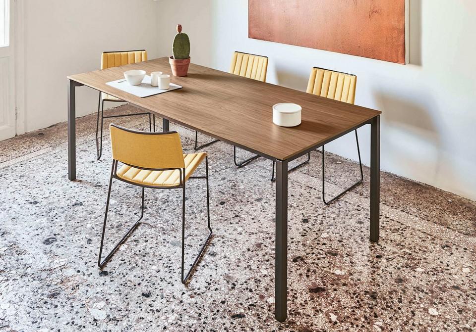 Tavolo allungabile More con gambe in acciaio color grafite e piano in legno finitura noce fiammato. Allunga in tinta
