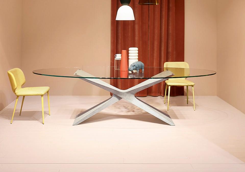 Tavolo Nexus con base in baydur effetto cemento grigio chiaro e piano in vetro trasparente