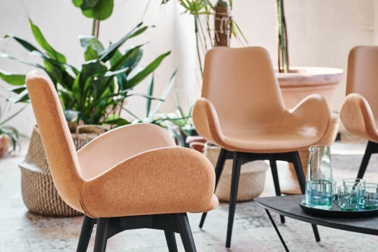 Dalia armchair with four-leg base in wood and cover in leather and pink fabric.
