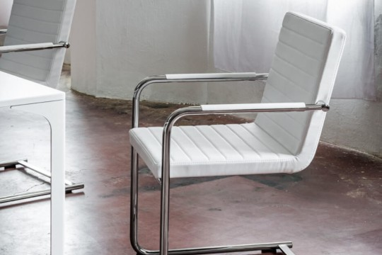 H5 design chair with padded seat covered in white fabric, the structure is in metal.