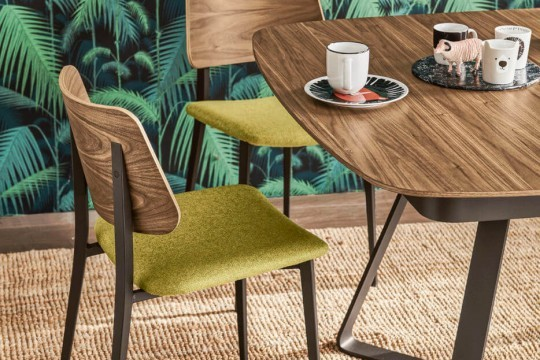 Joe restaurant chair with wooden back and green fabric seat. The base is formed by four metal legs