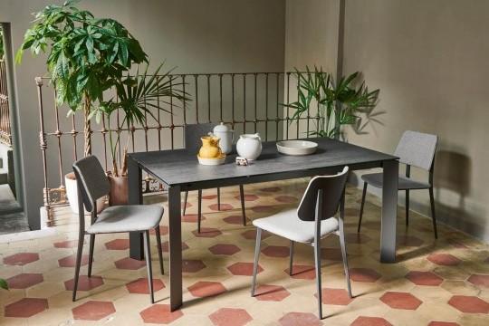 Sedia Joe Con base in metallo e schienale in legno. La sedia ha una seduta in tessuto grigio