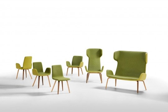 Light chair with seat covered in green fabric and back shell in light green. The base is made of wood