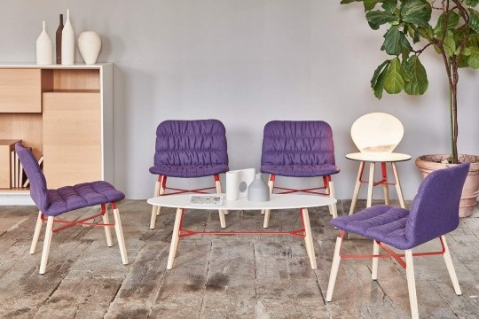 Lounge Liù with seat covered in purple fabric and legs in wood and red painted steel
