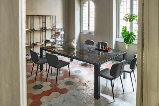 Tavolo quadrato allungabile Marcopolo con base a quattro gambe in metallo nero, piano e allunghe in cristalceramica effetto marmo noir desir
