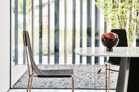 Mia dining chair with sled structure in rose gold colored metal and black Tuscan hide