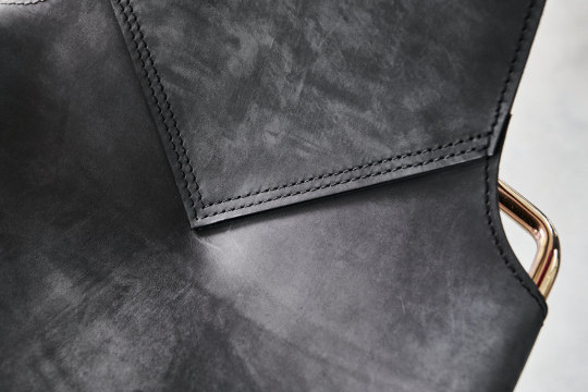 Detail of the seams of the Mia dinig chair in black Tuscan leather