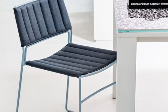 Slim chair with seat covered in blue fabric and blue metal frame