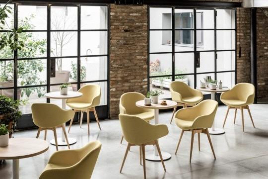 Sonny chaise de table avec accoudoir bas. Le siège est recouvert de tissu jaune et la base en bois
