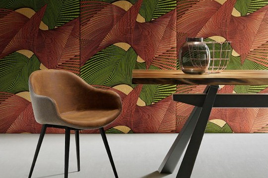 Fauteuil design Sonny avec assise en cuir marron et coque dorsale en tissu gris.