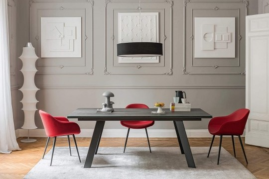 Sonny chair with armrests entirely covered in red fabric. The base is in metal