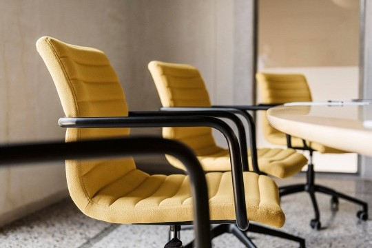 Détail du siège de la chaise Star avec assise en tissu jaune et accoudoir en métal