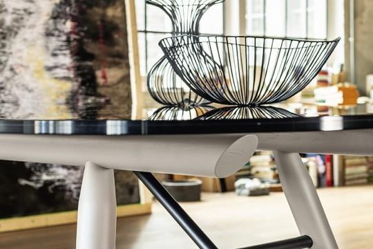Détail des pieds en bois de la table Suite et du plateau en verre