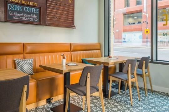 Sedie Joe con gambe in legno finiture rovere naturale e tessuto nel M Cafè dell'Hotel Indigo di Manchester