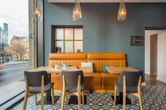 The Joe design chairs with wooden legs in natural oak finish and upholstered in fabric furnish the M Cafè of the Hotel Indigo in Manchester