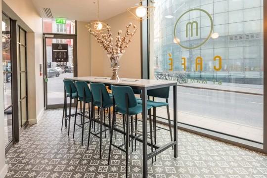 Gli sgabelli Joe con gambe in metallo e rivestimento in tessuto sono collocati nella zona nel bancone del M Cafè dell'Hotel Indigo di Manchester